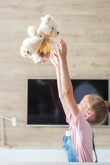 Красивая маленькая девочка на диване обнимает плюшевого мишку, концепция счастливого детства, игра в семье,