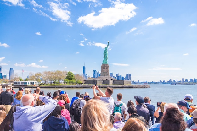 Люди делают фотографию статуи свободы, нью-йорк, штат нью-йорк, сша