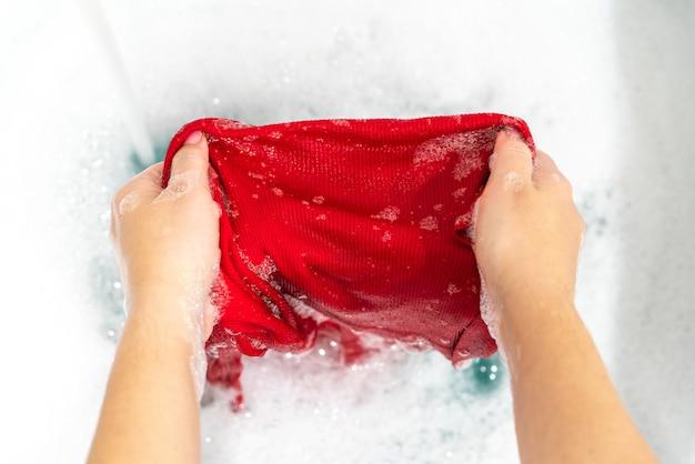 赤い服の手洗いで汚れを落とす
