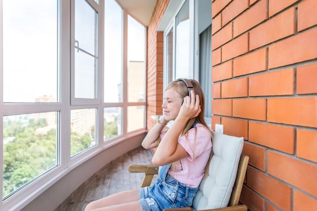 タブレットで彼女のヘッドフォンで音楽を聴いて楽しんでいる若い女の子