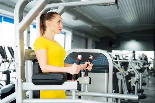 腹筋のトレーニングと足を上げる。フィットネス運動をしている若いかなり筋肉の女性。健康とスポーツライフスタイルのコンセプト。運動体。