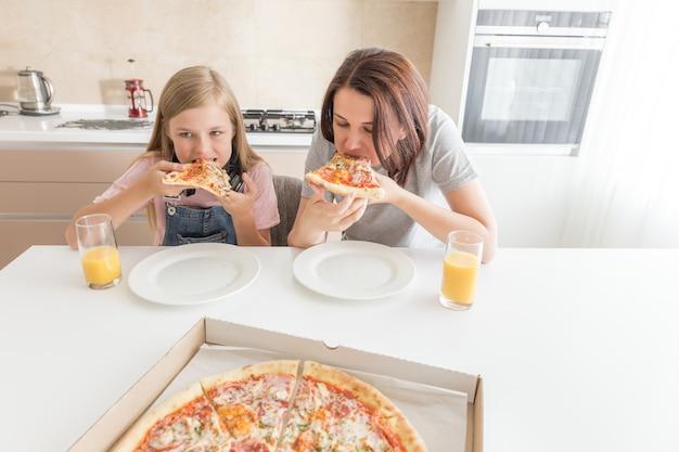 Мать и дочь сидят на кухне, едят пиццу и веселятся