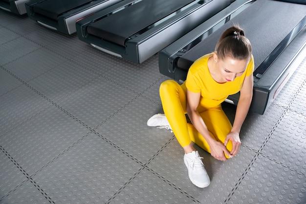 Молодая женщина с травмированным коленом сидит в тренажерном зале, чувствуя боль