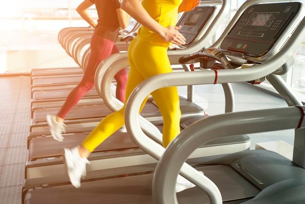 Две молодые женщины бегают по беговой дорожке в тренажерном зале