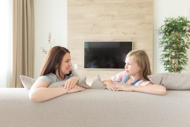 自宅のソファーにぴったりの母親と人と家族の概念幸せな笑みを浮かべて少女