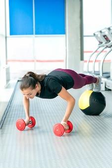 ジムで床のトレーニングをしている女性。ダンベルと薬のボール板をやっているフィットネス女の子