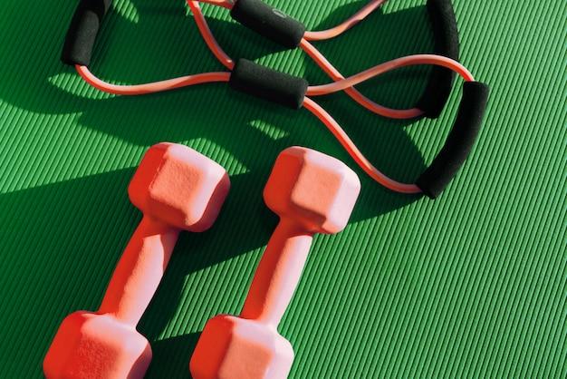 Резиновый эспандер и две гантели на зеленом коврике в фитнес-клубе