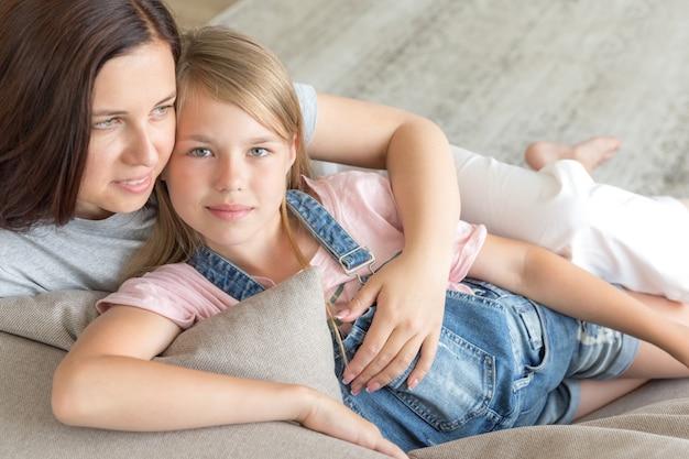母と笑みを浮かべて、幸せな家族の概念のソファに座って前の十代の娘