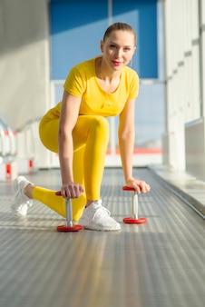 ダンベルで腕と上腕二頭筋を強化する準備ができているジムで身体的にフィットする女性