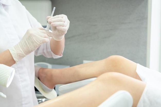 婦人科医と注射器は、婦人科の椅子で患者に注射を行います