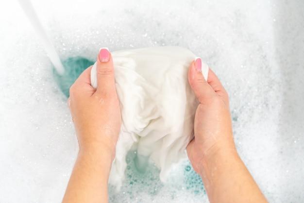 Ручная стирка белой одежды в раковине для отбеливания