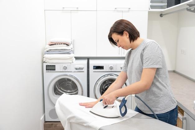 Молодая женщина гладит белую рубашку на борту в прачечной со стиральной машиной