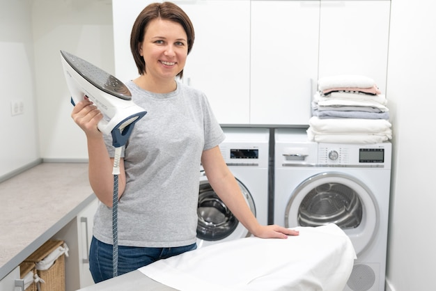 Женщина улыбается стоя возле гладильной доски в прачечной со стиральной машиной
