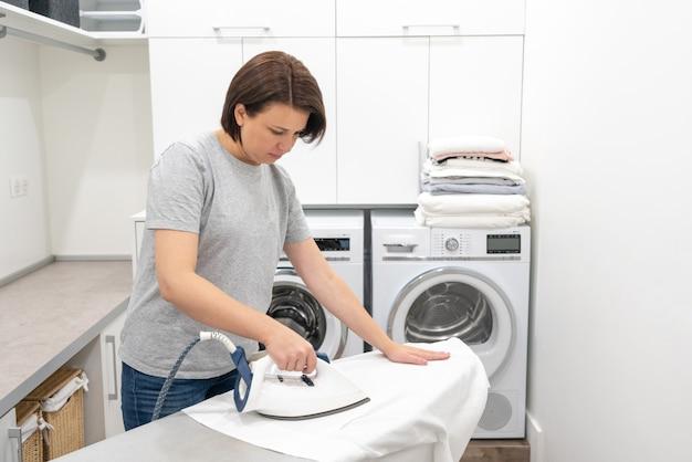 Гладильная белая рубашка на борту в прачечной со стиральной машиной