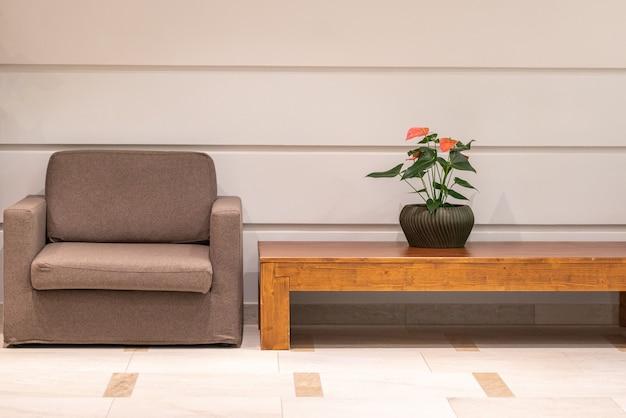 茶色の肘掛け椅子、木製のテーブル、白い壁の背景に花とホテルホールのインテリア