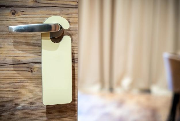 Пустой знак на ручке двери отеля для вашего текста