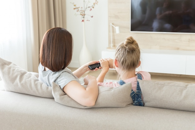 母と娘がテレビを見てソファの上に座って、リモートコントロールのために戦って