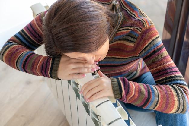 Женщина в пуловере сидит возле обогревателя радиатора и обнимает его
