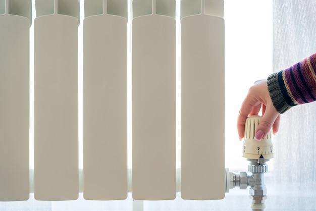 ラジエーター調整のクローズアップ。ラジエーターの温度を調整する女性の手