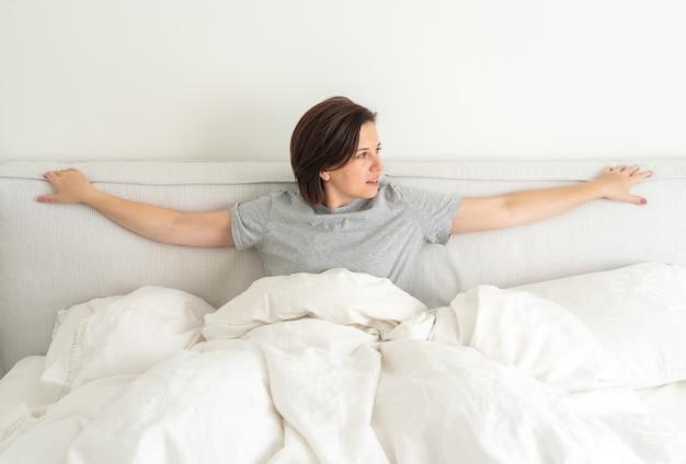 寝室のベッドに座っているパジャマを着て笑顔のブルネットの女性