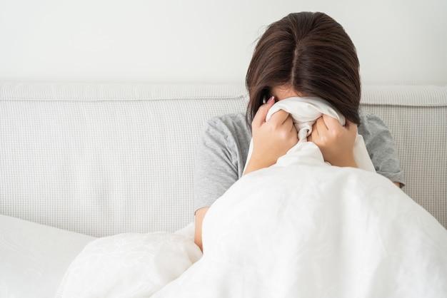 コピースペースで、自宅のベッドに座って動揺して悲しい若いブルネットの女性