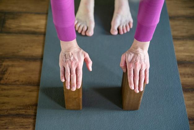 手で木製ブロックを使用してヨガのストレッチを行う女性、背骨と肩の柔軟性のための運動