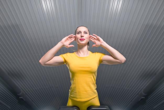 若いスポーティな女性のジムで腹筋マシンで行使、下からの眺め