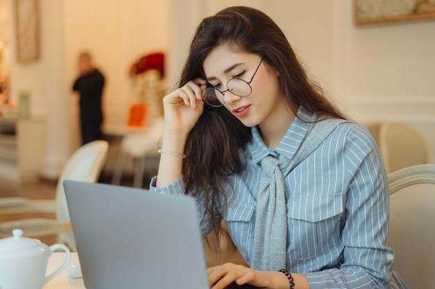 Милая азиатская женщина имея чашку чаю пока использующ портативный компьютер в кафе и касающся ее стеклам