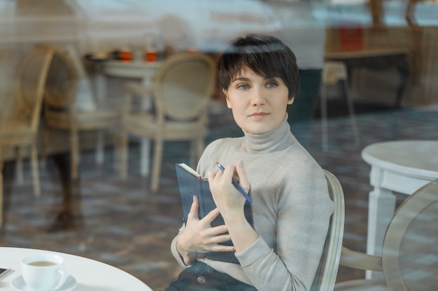 コーヒーブレーク中にメモ帳でメモを取ってカフェで若い女性を笑顔、窓からすを見る