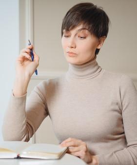 スタイリッシュなカフェでレクリエーションの時間を楽しんでいるメモ帳で行う計画とライティングリストを書く手にペンで魅力的な若い女性