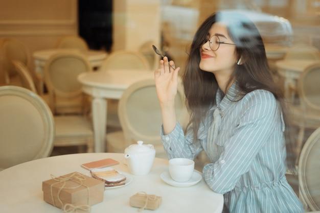 Красивая азиатская девушка наслаждаясь горячим чаем в кафе пока слушающ музыка на наушниках, взгляд через стекло окна