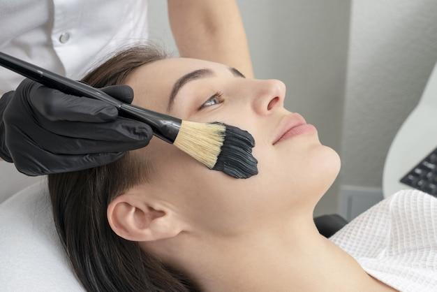 カーボンピールの美しい女性の顔にブラックマスクを適用する美容師