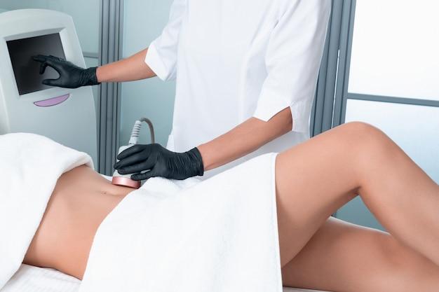 超音波キャビテーションボディコンター処理。ビューティーサロンで彼女の足に抗セルライトと抗脂肪療法を得る女性