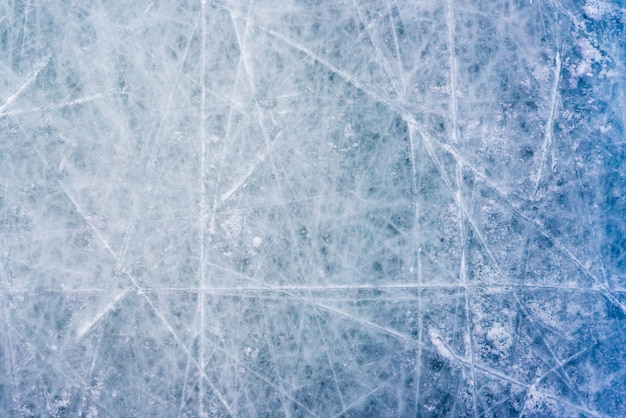 スケートやホッケーのマークと氷の背景、傷のあるリンクの表面の青いテクスチャ