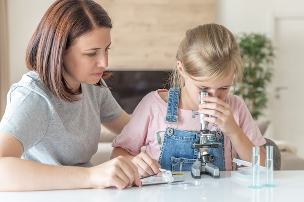 母と若い娘が自宅で顕微鏡でいくつかの実験を行う