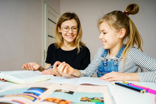 母と娘が一緒に宿題をして、スタイディングと学習の概念、学校のタスクを行う