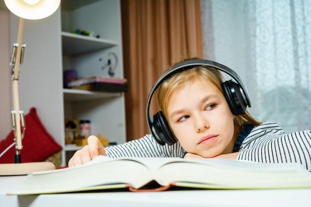 オーディオブックを聞いて、学校の宿題、学習、勉強の概念をやっている女の子