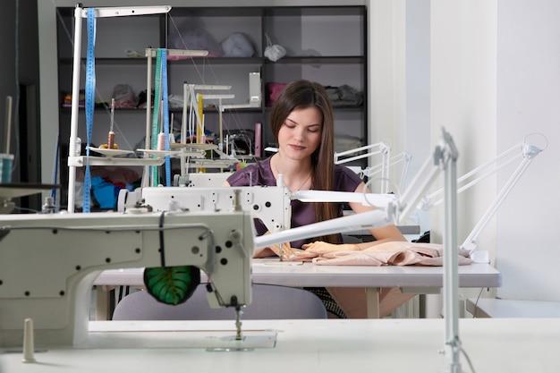 Юная портниха шьет одежду на швейной машине в ателье