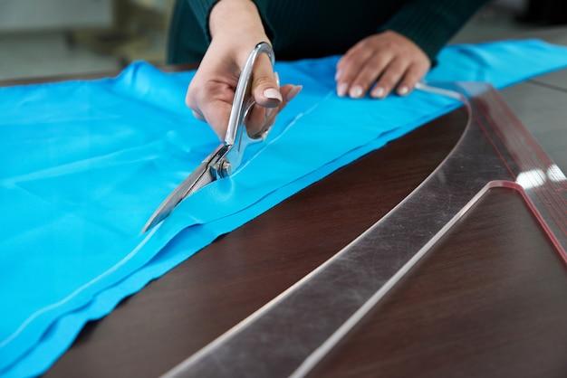 Портниха порезает синюю ткань в ателье ателье