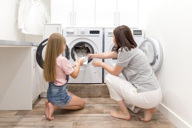 洗濯機と乾燥機の近くのランドリールームで母と娘のヘルパーがきれいな服を脱いで