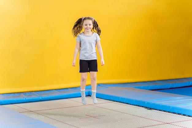 Счастливая маленькая девочка прыгает на батуте в фитнес-центре