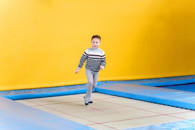 Счастливые улыбающиеся маленькие дети прыгают на батуте в помещении в развлекательном центре