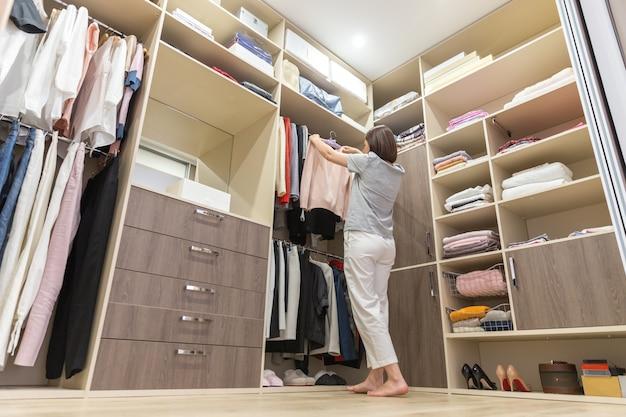 Красивая девушка выбирает одежду в своей гардеробной