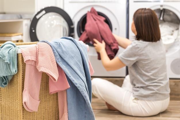 Женщина загружает грязную одежду в стиральную машину для стирки в современном подсобном помещении