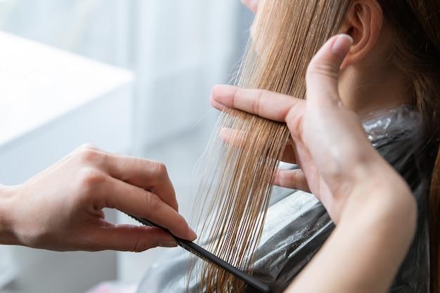 美容師はヘアサロンで金髪の若い女性の髪をカット
