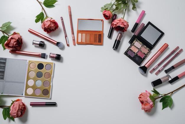 Декоративная плоская композиция с косметикой и цветами. плоская планировка, вид сверху на белом фоне