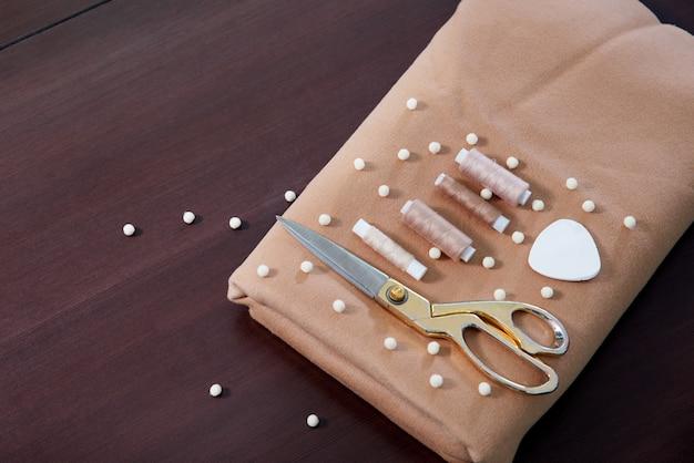 Группа швейных объектов, лежащих на деревянном столе, концепция ателье