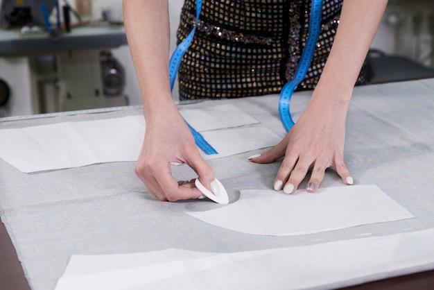 Портной за работой, рисование линии на ткани мелом в ателье ателье