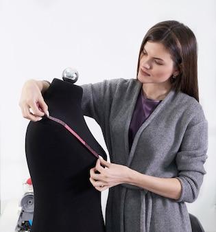 Брюнетка швея измеряет черный манекен в мастерской, ателье