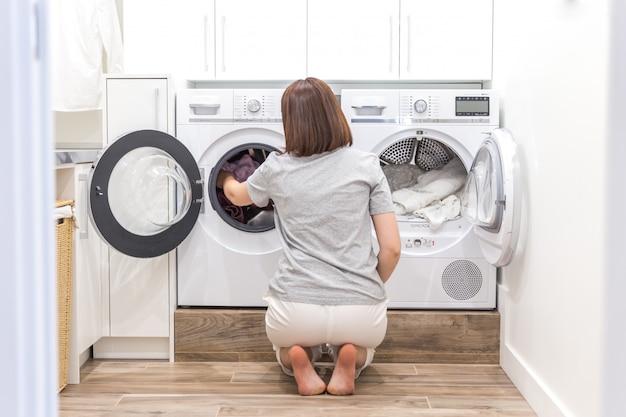 Женщина кладет одежду в стиральную машину для стирки